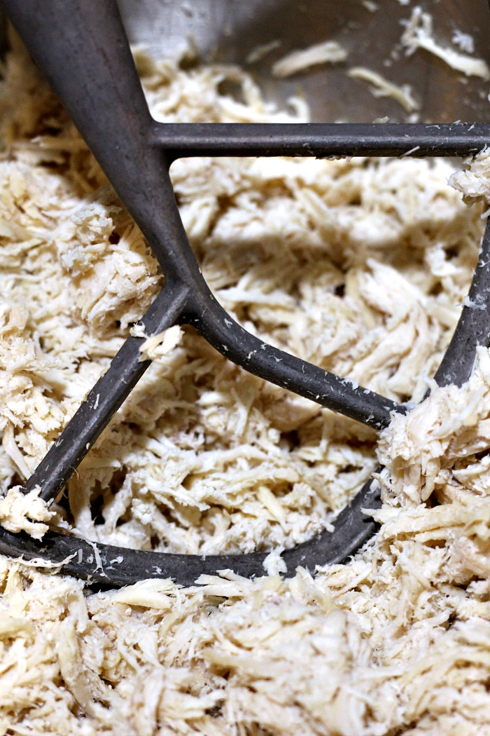 Crock Pot Shredded Chicken is a time saver in the kitchen for dinners and healthy way to prep chicken! Use your kitchen aid mixer for easy shredding.