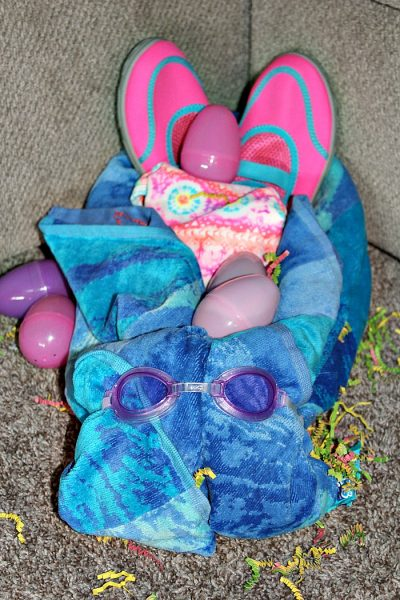 These Easter Beach Towel Bunnies are the perfect alternative to a traditional Easter basket!! Make them with everything the kids need for summer beach towel, swimsuit, swim goggles, flip flops, floaties, water shoes, or any other accessory.