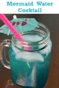 This Mermaid Water Cocktail is full of flavor and an easy cocktail to make at home to take yourself to a tropical getaway at home as well! Make a pitcher to take to a get-together or a night in the girls!